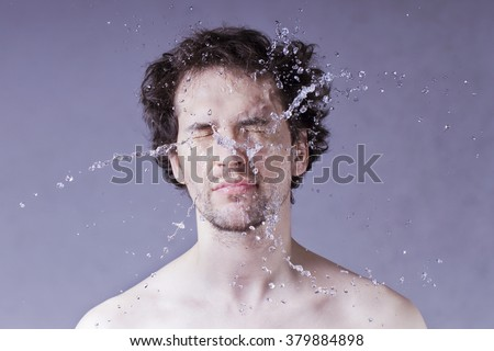 Washing up. Handsome man with splashing water on his face. - stock photo