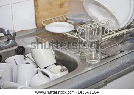 Washing-up in office kitchen sink - stock photo
