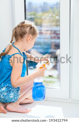 Washing windows with a rag and spray, small girl in blue dress - stock photo