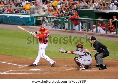 WASHINGTON - AUGUST 14: Adam Dunn of the Washington Nationals swings at a pitch in the Nationals' home game against the Arizona Diamondbacks on August 14, 2010 in Washington. - stock photo