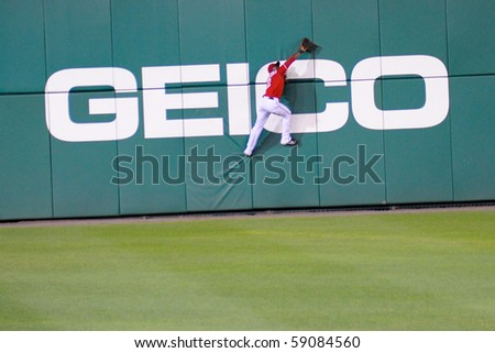 WASHINGTON - AUGUST 14: Roger Bernadina of the Washington Nationals attempts a catch at the wall in the Nationals' home game against the Arizona Diamondbacks on August 14, 2010 in Washington. - stock photo