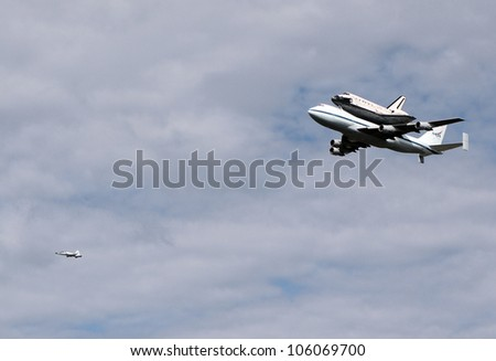 WASHINGTON, D.C. - APRIL 17: Space Shuttle Discovery on top of a Boeing 747, escorted by a Northrop T-38 chase plane, en route to Dulles Airport in Washington D.C. on April 17, 2012. - stock photo