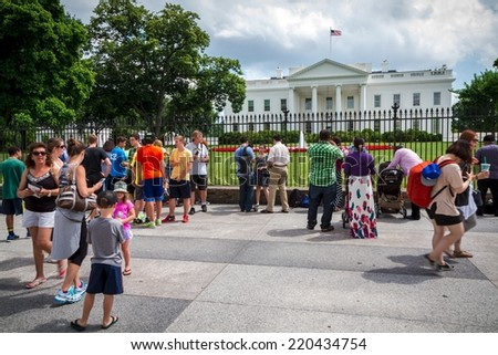 WASHINGTON, D.C. - JUNE 11, 2014: Tourists in front of the White House. It is the official residence and principal workplace of the President of the United States. - stock photo