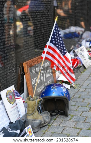 WASHINGTON, D.C. - MAY 26, 2014: People visit and lay flowers and other souvenirs  at the Vietnam Veterans Memorial on May 26, 2014, in Washington, D.C. - stock photo