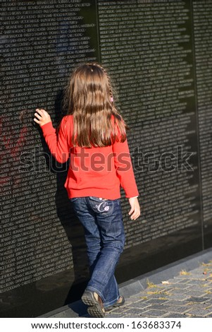 WASHINGTON, D.C. - OCT 29, 2013: Unidentified little girl looks for a name on the wall at Vietnam Veterans Memorial on October 29, 2013, in Washington, D.C. - stock photo
