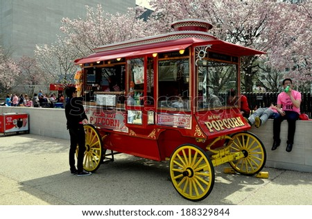 Washington, DC - April 11, 2014:  Popcorn Vendor's classic wagon standing in front of the NASA Museum with its grove of flowering cherry trees - stock photo