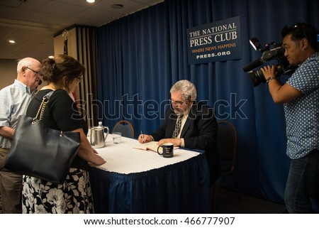 Washington, DC - August 4, 2016: Pulitzer Prize reporter David Cay Johnston signs copies of his new book, The Making of Donald Trump, at the National Press Club. Japanese cameraman takes video.