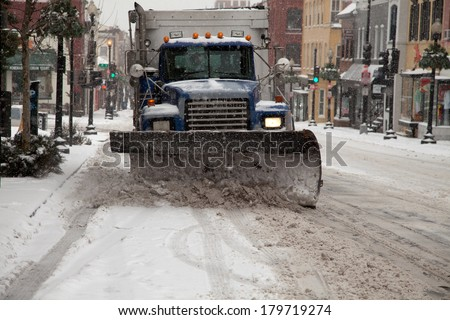 WASHINGTON, DC - FEBRUARY 3: Winter storm of the Mid Atlantic on February 3, 2014 in Washington, DC. Truck plowing Wisconsin Ave. in Georgetown. The government, stores and companies where closed. - stock photo