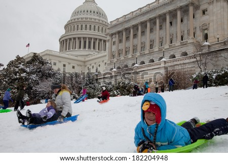 WASHINGTON, DC - MARCH 17: Unexpected snow day on March 17, 2014 in Washington, DC. Schools were closed, children and adults are playing with their snow sled on the US Capitol lawn. - stock photo
