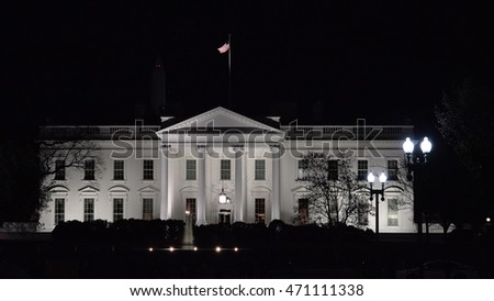 WASHINGTON, DC - MARCH 2016: White House at night, American flag flying. White House remains lighted for evening tourists.