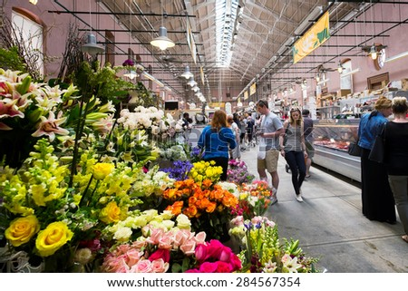 WASHINGTON DC-May 24, 2015: Inside the historic Eastern Market in the Capitol Hill neighborhood, first opened in 1805. Image of shoppers browsing. Colorful flower stand in the foreground. - stock photo