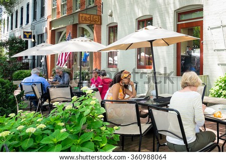 WASHINGTON DC - MAY 24, 2015: People at outdoor sidewalk cafes in the Capitol Hill neighborhood. The area is a popular destination for its shops, restaurants and the historic Eastern Market next door. - stock photo