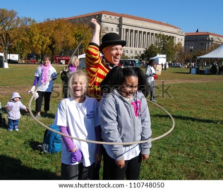 WASHINGTON, DC - NOVEMBER  07: Alzheimer's Walk Event on November 07, 2011 in Washington DC ,USA. Unidentified Children playing with a Circus man during a fund raising event to end Alzheimer's disease. - stock photo