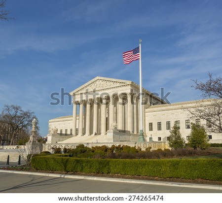 WASHINGTON, DC, USA - APRIL 06, 2015: United States Supreme Court building exterior and american flag.