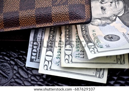WASHINGTON DC, USA - JULY 31, 2017: Louis Vuitton mens wallet filled with cash.