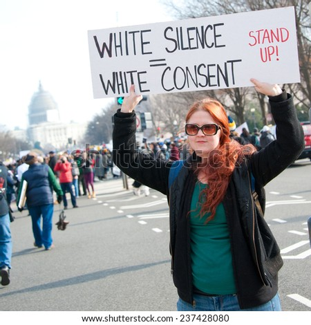 WASHINGTON - DECEMBER 13: A protester holds a sign during a march against police shootings and racism during a rally in  Washington, DC on December 13, 2014  - stock photo