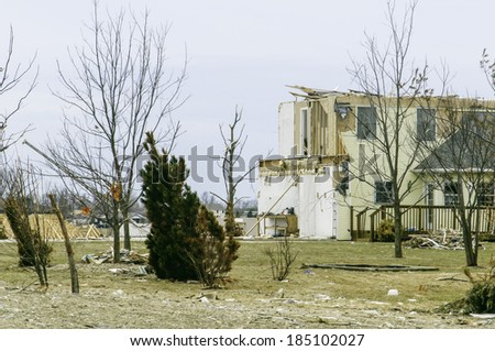 WASHINGTON, ILLINOIS, USA - MARCH 31, 2014: In the aftermath of a November tornado, signs of recovery appear as a robin perches on a bare tree (at left) amid scenes of destruction and reconstruction.