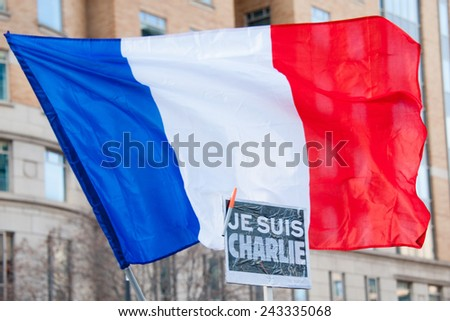 WASHINGTON - JANUARY 11: A sign and flag stand out during a silent protest against the terror attacks in Paris in Washington, DC on January 11, 2015 - stock photo