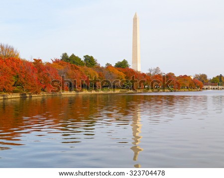 Washington Monument and the Tidal Basin in autumn. The Monument is surrounded by trees in the colorful foliage during the Fall in DC, USA. - stock photo