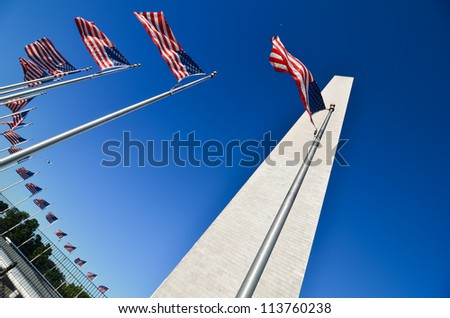 Washington Monument with waving United States flags on flagpoles - Washington DC United States - stock photo