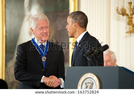 Washington - November 20: Former President Bill Clinton shakes hands with President Obama after receiving the Presidential Medal of Freedom at The White House on November 20, 2013 in Washington, DC.  - stock photo