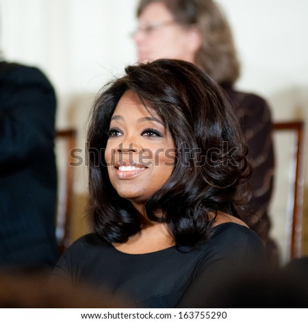 WASHINGTON - NOVEMBER 20: Oprah Winfrey listens to President Barack Obama at the Presidential Medal of Freedom ceremony at the White House November 20, 2013 in Washington, D.C. - stock photo