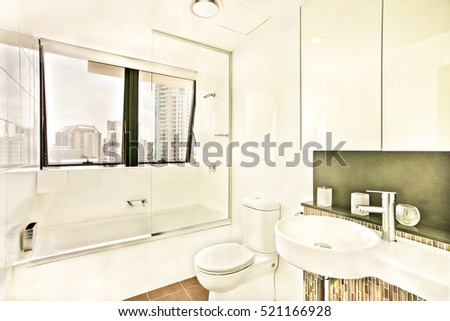Washroom near glass windows with tiles, wash area and toilet decorated using a light, ceramic bottles with soap on countertop close to white washstand, the mirror is colorful and clean.