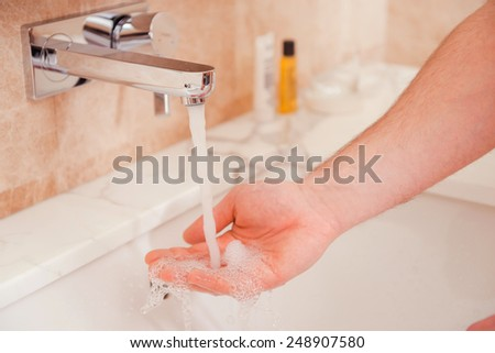 Wasshing hands. Close-up of man washing hands in bathroom