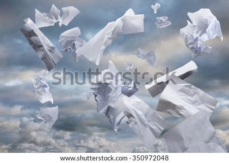 Waste paper carried up by the wind, blows across a cloudy sky - stock photo
