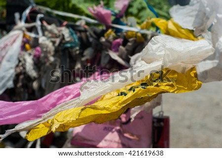 Waste plastic  hank on sling fence  had swinging while have windy .   - stock photo