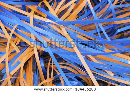 waste plastic straps used for construction material in blue and orange - stock photo