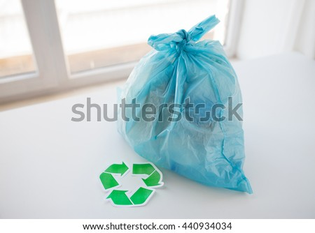 waste recycling, reuse, garbage disposal, environment and ecology concept - close up of rubbish bag with trash or garbage and green recycle symbol at home - stock photo