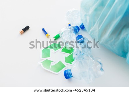 waste recycling, reuse, garbage disposal, environment and ecology concept - close up of used crashed plastic water bottles and batteries with rubbish bag and green recycle symbol - stock photo