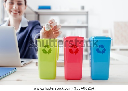Waste separate collection and recycling in the workplace, office worker sorting garbage using different trash bins - stock photo