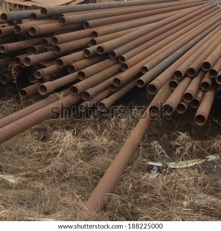 Waste steel drill stem strewn about awaiting recycling in a scrap yard east of Edmonton, Alberta - stock photo
