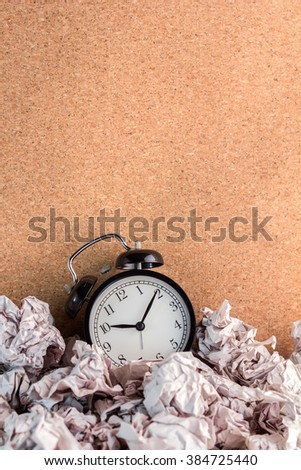 waste time concept alarm clock with trash paper - stock photo