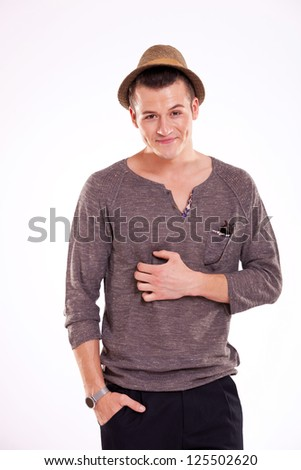 waste-up picture of a young casual man scratching his belly and holding a hand in his pocket, while looking at the camera, on a light background