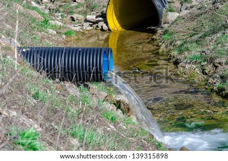 Waste water pipe polluting environment - stock photo