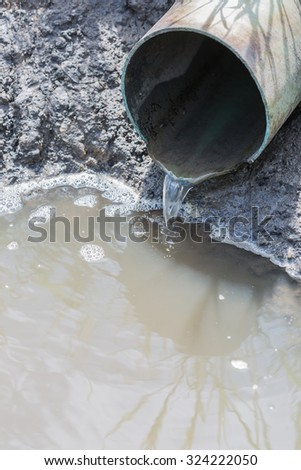 waste water running slow from a pipeline - stock photo