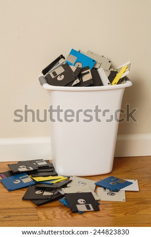 Wastebasket overflowing with 3.5-inch floppy disks. - stock photo
