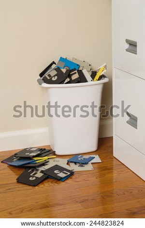 Wastebasket overflowing with 3.5-inch floppy disks beside a file cabinet. - stock photo
