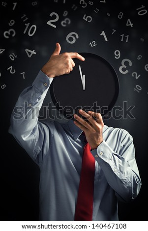 Wasting time. Businessman with clock in front of his head with not enough time to finish the job. - stock photo