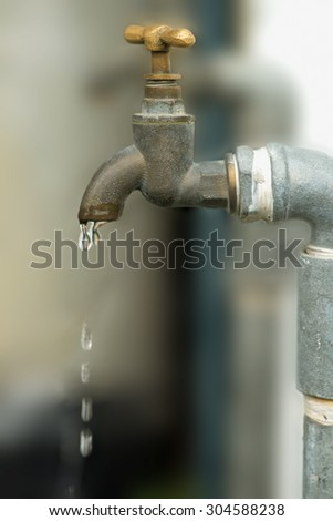 Wasting water - water drop from water tap - stock photo