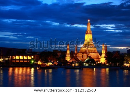 Wat Arun gold lighting after sunset with blue sky - stock photo