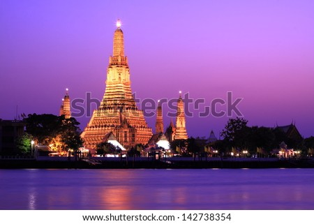 Wat Arun, Twilight view of Wat Arun across Chao Phraya River during sunset in Bangkok, Thailand - stock photo