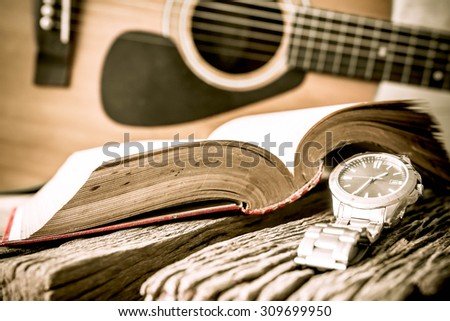 Watch and guitar with open book on old wooden table, vintage style. - stock photo