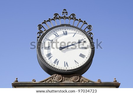 Watch classic wrought iron metal on blue background - stock photo