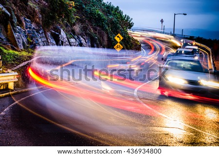 Watch for cyclists. Speeding traffic with light and motion blur near watch for cyclists sign. There is no bike lane. Launceston, Tasmania, Australia. - stock photo