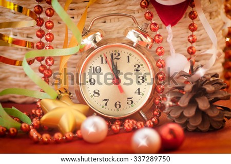 watch hands by 12 hours and Christmas toys background closeup effect has been applied - stock photo