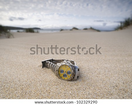 watch lost on the beach. The clock is on the sand